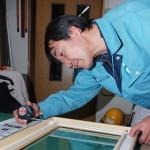 1階の作業台で額縁の寸法を測りながら作製する加藤さん 【】写真をクリックで拡大